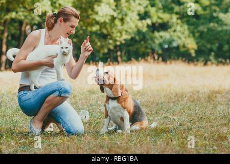 In der Nähe von attraktiven passende Frau in der Nähe von Ihrem Hund kniend, ihn Training. Junge Mädchen, dass weiße Katze geben Kommandos und Anfragen zu Ihrem Hund, im Freien - Stockfoto