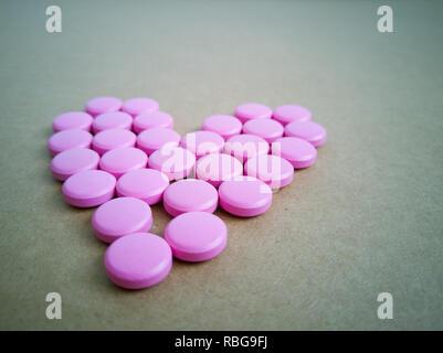 Rosa Pillen in Form eines Herzens auf braunem Hintergrund. farbige Drogen. Konzept - Herz-Krankheit, Herz-Kreislauf-Erkrankungen und Medikamente, Kardiologie, Valentine - Stockfoto