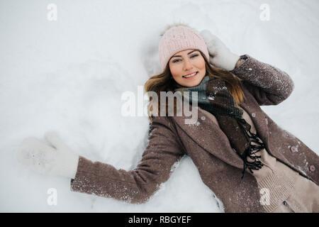 Foto des Blonden in hat liegt im Schnee zu Fuß - Stockfoto