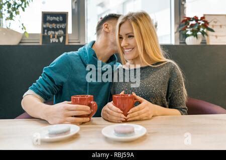 Junge glückliches Paar in Liebe im Café, ein junger Mann und eine Frau zusammen lächeln umarmen Kaffee trinken Kaffee.
