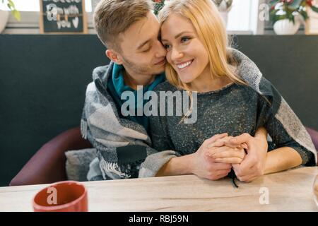 Herbst Winter Porträt der jungen umarmen Paar. Junger Mann und Frau im Cafe unter warmen Wolldecke Kaffee trinken Kaffee, glücklich zusammen.