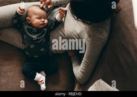 Baby in einen tiefen Schlaf in den Schoß seiner Mutter zu Hause. Mutter sitzt auf der Couch, mit ihrem Baby schlafen in ihren Schoß und seinen Kopf zu berühren. - Stockfoto