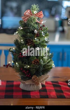 Ein Miniatur Tischplatte Weihnachtsbaum mit sackleinen auf einem roten und schwarzen Tabelle Runner. Indoor Weihnachten Dekor. - Stockfoto