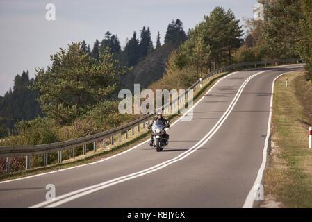 Motorradfahrer in schwarzem Leder outfit Reiten cruiser Motorrad entlang Twisted Straße auf die hellen sonnigen Sommertag auf dem Hintergrund der nebligen entfernte grün bewaldeten Hügeln unter blauen Morgenhimmel. - Stockfoto