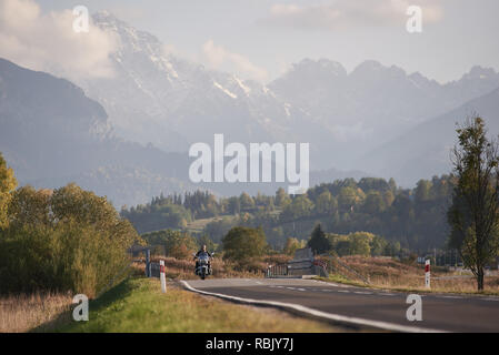 Motorradfahrer reiten leistungsstarke High-speed Motorrad auf Blau nebligen Berge mit schneebedeckten Gipfeln und hellen Sommer sky copy Space Hintergrund. - Stockfoto
