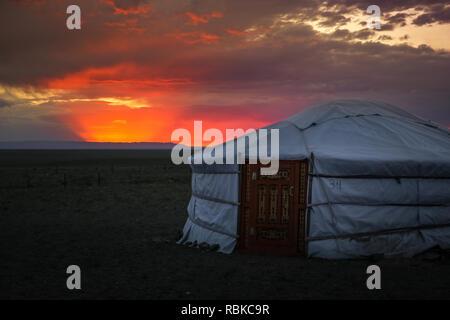 Traditionelle mongolische Gehäuse/Jurte bei Sonnenuntergang mit dramatischen Wolkenhimmel in der Wüste Gobi in der Nähe der Flaming Cliffs (Bajandsag, Wüste Gobi, Mongolei) - Stockfoto