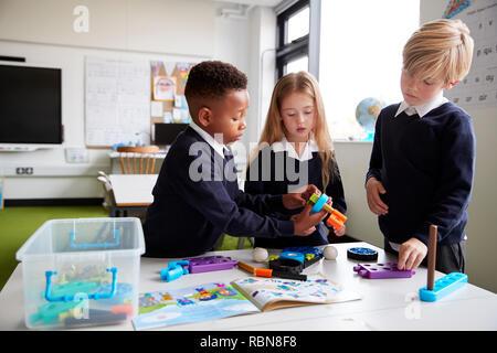 Ein Mädchen und zwei Jungen stehen an einem Tisch in einer Grundschule Klassenzimmer gemeinsam mit Spielzeug Bau Blöcke, in der Nähe - Stockfoto