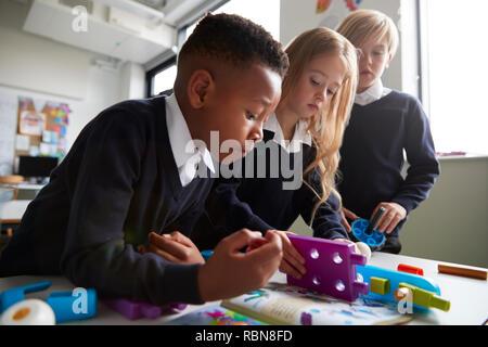 Nahaufnahme von drei Grundschüler gemeinsam mit Spielzeug Bau Blöcke in einem Klassenzimmer, niedrigen Winkel, Seitenansicht - Stockfoto