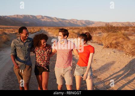 Vier junge erwachsene Freunde gehen auf eine Wüste Straße, in der Nähe - Stockfoto