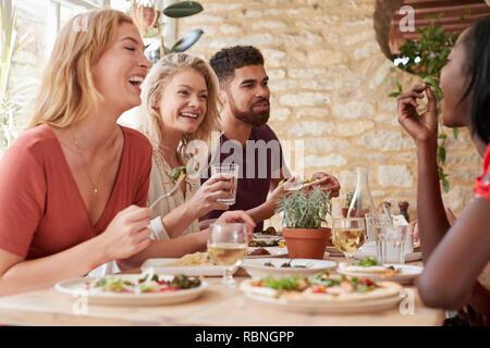 Vier junge erwachsene Freunde Essen in einem Restaurant, in der Nähe - Stockfoto