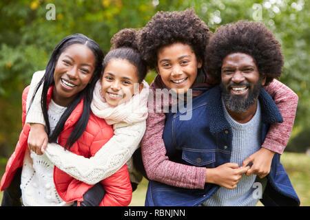 Mischlinge Familie lächelnd in die Kamera, Eltern, die Kinder in die Landschaft, in der Nähe Netzwerk zugreift. Stockfoto
