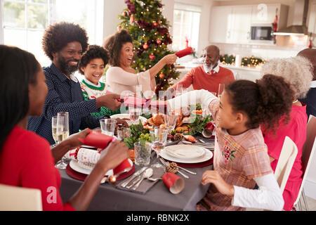 Gemischte Rasse, multi-generation Familie Spaß Cracker ziehen am Weihnachtsessen Tabelle - Stockfoto