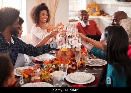 Multi-Generation gemischten Rennen Familie ihre Gläser heben ein Toast auf den Thanksgiving Dinner Tabelle zu machen - Stockfoto