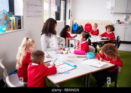 Junge weibliche Infant School Lehrer an einem Tisch sitzen in einem Klassenzimmer mit ihren Schülern Stockfoto