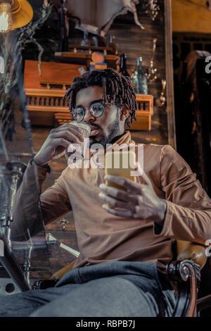 Schöne bärtige Freiberufler trinken Kakao im Cafe - Stockfoto