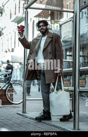 Fröhliche brunette männliche Person holding Pappbecher - Stockfoto