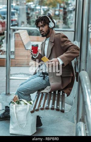 Brünett Mann sein Telefon halten in der linken Hand konzentriert - Stockfoto