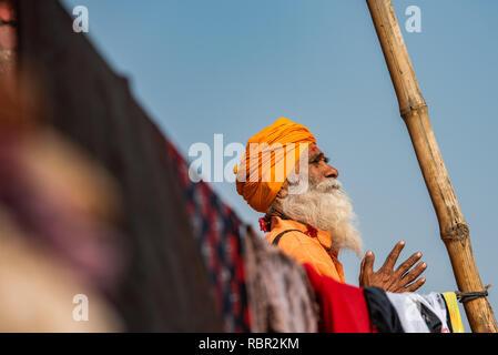 Ein heiliger Mann im Gebet die Hände gefaltet, die von einem Pol und Kleidung gerahmt in Varanasi, Indien