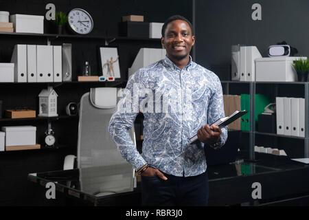 Porträt junger schwarzer Geschäftsmann mit finanziellen Unterlagen in seinen Händen in der Nähe von Tabelle im Büro - Stockfoto