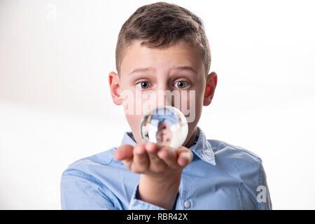 Junge sieht sein Spiegelbild in einem Glas Kugel direkt vor seinem Gesicht vor einem weißen Hintergrund