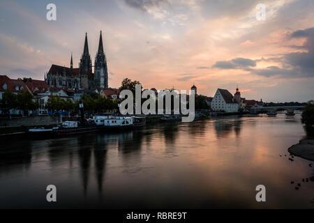 Es ist Dom St. Peter in Regensburg, Bayern, Deutschland. Stadtbild Bild über die Donau bei Sonnenuntergang. - Stockfoto