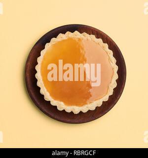 Caramel verglaste tart auf Gelb, Ansicht von oben isoliert. - Stockfoto