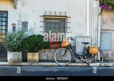 Fahrrad mit weidenkörbe auf der Straße in Orbetello auf der Halbinsel Argentario in der Toskana. Italien - Stockfoto