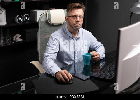 Business Mann mit Brille im Büro am Computer Tisch und trinken Kaffee von Helle Schale - Stockfoto