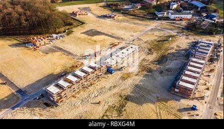 Wolfsburg, Deutschland, Januar 3., 2019: Luftaufnahme der Schale ein großes Reihenhaus in einem Neubaugebiet neben einem alten Dorfkern - Stockfoto