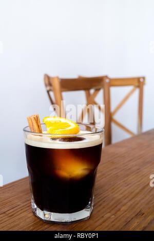 Kalter Kaffee brühen mit Zitrone und Zimt dienen auf hölzernen Tisch und Stühle im Café am Morgen. beliebten Eiskaffee Menü im Sommer. - Stockfoto