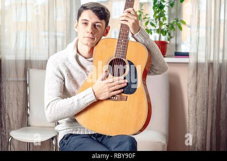 Junge attraktive männliche Musiker sitzt auf einem Stuhl, eine akustische Gitarre. Das Konzept der Musik als Hobby - Stockfoto
