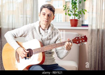 Junge attraktive männliche Musiker sitzt auf einem Stuhl spielen akustische Gitarre. Das Konzept der Musik als Hobby - Stockfoto