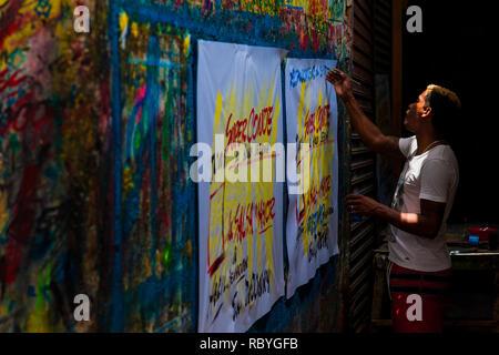 Eine kolumbianische Schildermaler schreibt mit einer Bürste während auf Musik Party Poster im Zeichen der Malerei Workshop in Cartagena, Kolumbien. - Stockfoto
