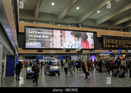 Uber taxi elektronische Werbung Plakatwerbung das Uber App für Mobiltelefone in Euston Bahnhofshalle in London England UK KATHY DEWITT - Stockfoto