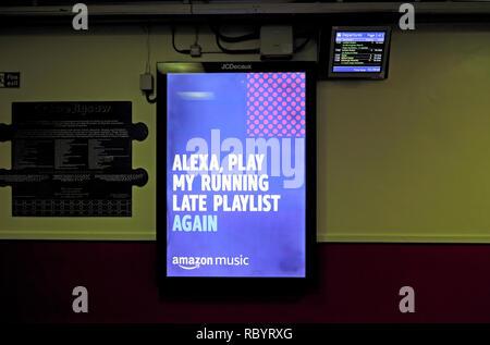 ' Alexa Spielen meine Verspätung Wiedergabeliste wieder 'Amazon Musik Werbung auf eine elektronische Anzeigentafel auf einem Bahnhof in Großbritannien Großbritannien KATHY DEWITT - Stockfoto