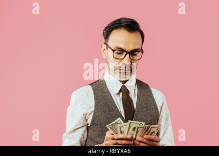 Reifer Mann zählen Geld, auf Pink Studio Hintergrund isoliert - Stockfoto