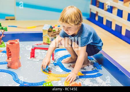Ein Junge spielt mit einem Spielzeug Eisenbahn - Stockfoto