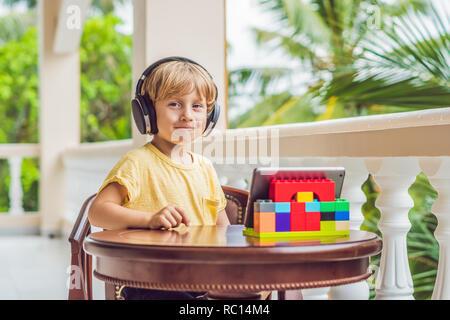Junge in Tropen im Gespräch mit Freunden und Familie auf Video Anruf über eine Tablette und kabellose Kopfhörer - Stockfoto