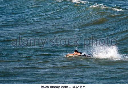 Ein Mann in einem wet-suit Paddeln sein Surfbrett eine Welle zu erwischen, Salzwasser treten und allein im Ozean; bei Turners Beach, Yamba, NSW, Australien. - Stockfoto