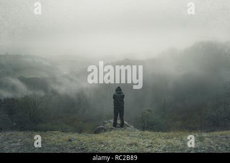 Ein einsamer hooded Abbildung auf einem Hügel, mit Blick über die Landschaft an einem nebligen, regnerischen Wintern. Mit einer bewussten Grunge, körnig, Stumm bearbeiten. - Stockfoto