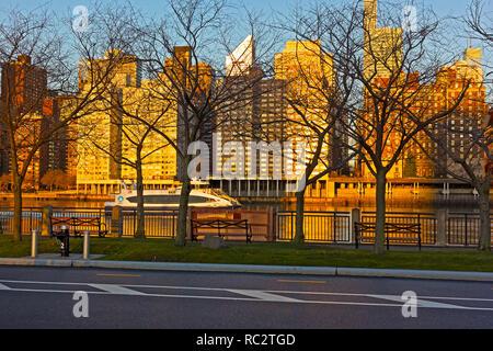 East River Waterway und Skyline von Manhattan bei Sonnenaufgang in New York, USA. Urban Panorama in goldenen Farben des frühen Morgens im Winter. - Stockfoto