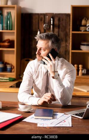 Beschäftigter Mann sprechen per Telefon in der Küche - Stockfoto