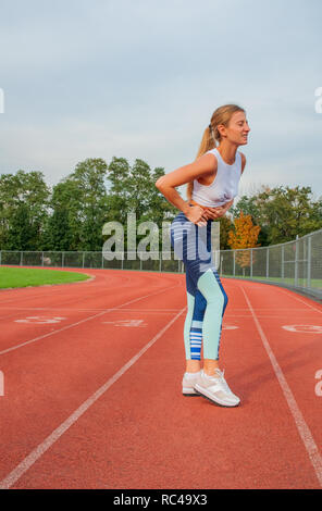 Athletische Frau auf der Laufstrecke hat Krämpfe während des Trainings - Stockfoto