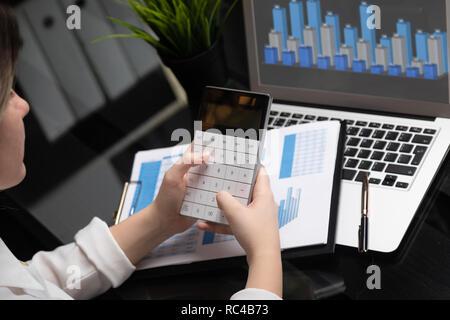 Geschäftsfrau Investment Consultant analysieren Unternehmen Geschäftsbericht Bilanz arbeiten mit Rechner und Laptop - Stockfoto