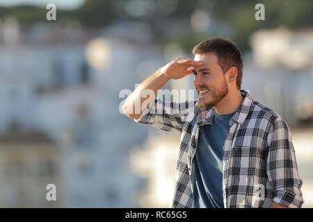 Glückliche Menschen Scouting mit der Hand auf die Stirn nach vorne in einer Stadt suchen - Stockfoto