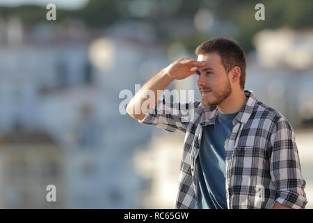 Ernster mann Scouting mit der Hand in die Stirn nach vorne in einer Stadt suchen - Stockfoto