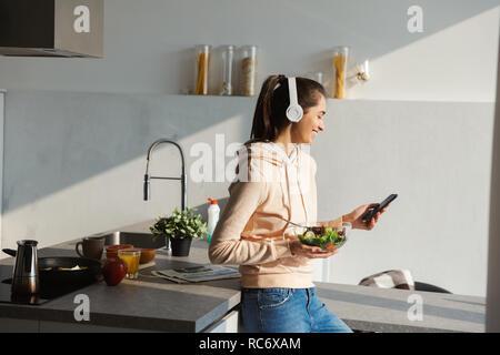 Fröhlicher junger Mädchen Musik hören mit Kopfhörern in der Küche zu Hause, Essen Salat aus einer Schüssel - Stockfoto