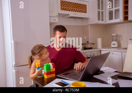 Besetzt männlichen Arbeiten mit Computer während der Suche nach seiner Tochter. - Stockfoto