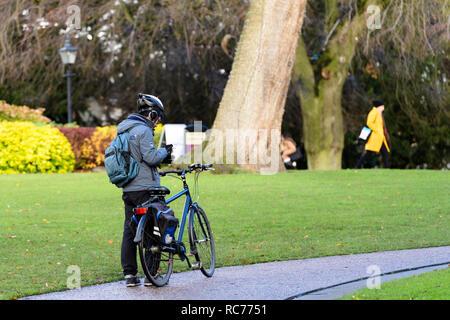 Männliche Radfahrer in Helm ist Gehorsam park Regeln & hat abmontiert, stehend mit Rad & Blick auf Telefon-Museum Gardens, York, Yorkshire, England, UK. - Stockfoto