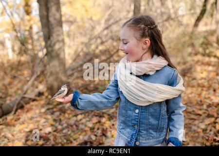 Kleines Mädchen mit Vogel auf Palm im Wald - Stockfoto